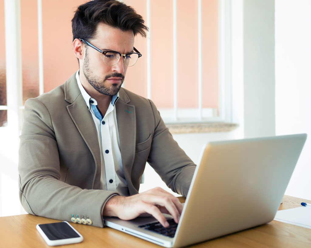 handsome-young-business-man-working-with-laptop-in-6G9V222.jpg